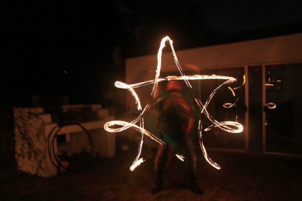 Duncan Greenwood spinning fire flower sticks in 2012